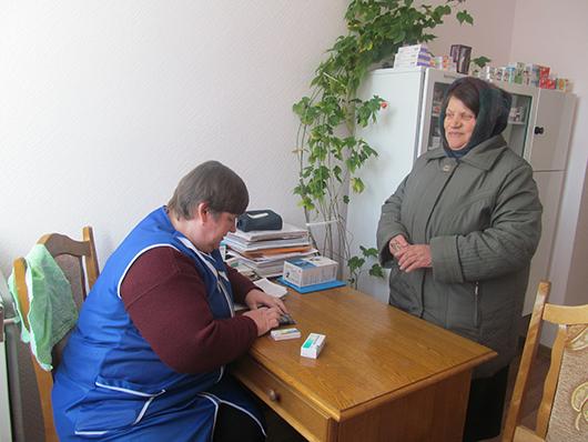 Санитарка Ольга Ананьевна Какора в аптечном пункте отпускает лекарство.