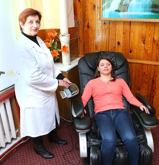 Медсестра ФТК Т.С.Музыченко проводит процедуру массажа контролеру Н.Г.Белошицкой.