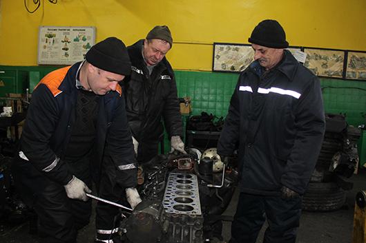 Слесари П.П.Латонин, В.П.Рудницкий и А.Е.Царук  ремонтируют двигатель.
