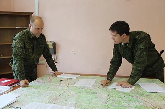 Военный комиссар подполковник В.В.Кобраль и старший офицер мобилизационного отдела старший лейтенант Б.С.Куприенко занимаются планированием поставки мобилизационных ресурсов.