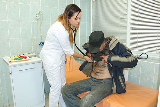 Врач Е.О.Гуляева осматривает пациента.