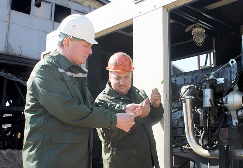 Главный механик А .Т. Свириденко и машинист буровых установок на нефть и газ В. А. Туровец проводят техобслуживание электростанции.